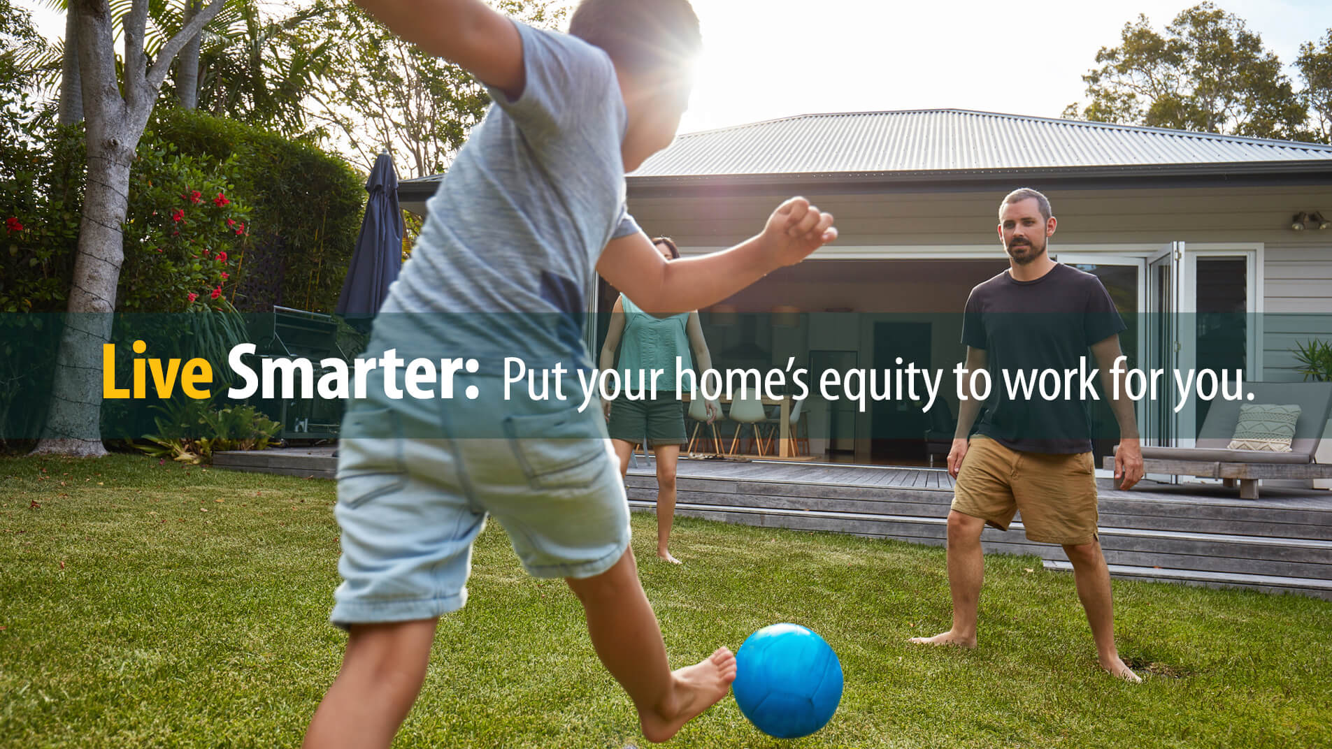 Dad, son play soccer in yard of home from which they will borrow against home equity